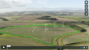 Aerial shot of a field with digital text superimposed